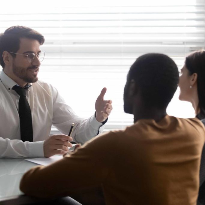 Confident male lawyer or financial expert explaining contract details, making offer to involved multiracial married couple. Happy mixed race spouse listening to professional broker or bank worker.